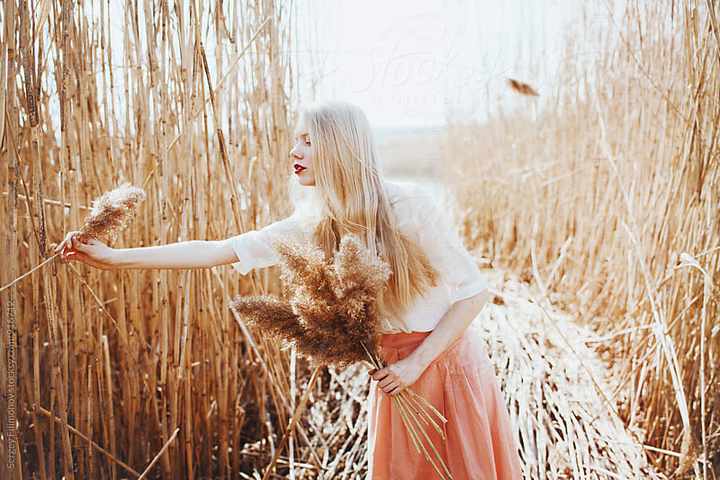 Young blonde girl collects grass in the field by Sergey Filimonov for Stocksy United