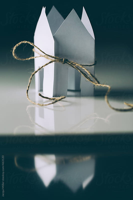 White paper houses tied up with string - with reflection by Jacqui Miller for Stocksy United