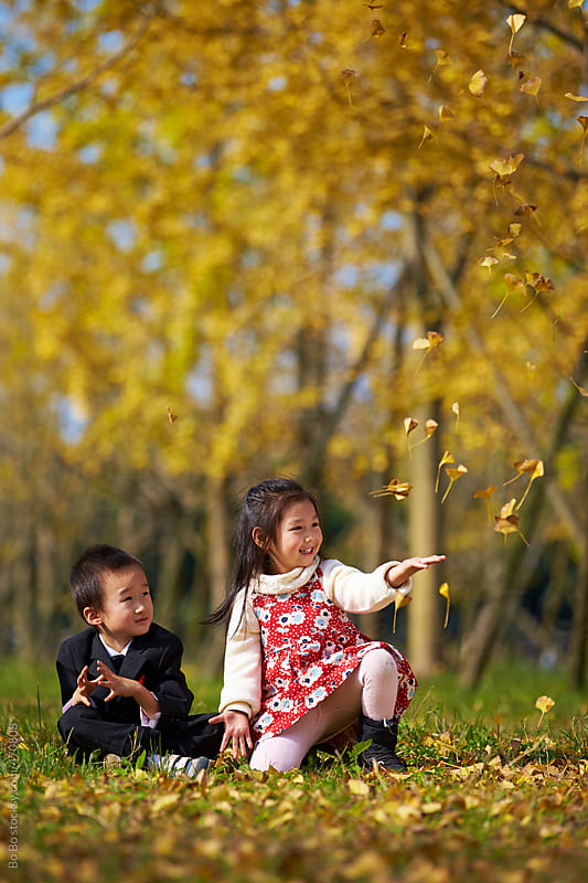 two little kids together in the autumn park by Bo Bo for Stocksy United