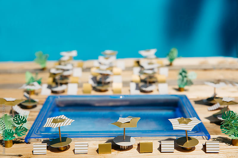 Pool and summer tools around it in front of a blue wall made of paper by Beatrix Boros for Stocksy United