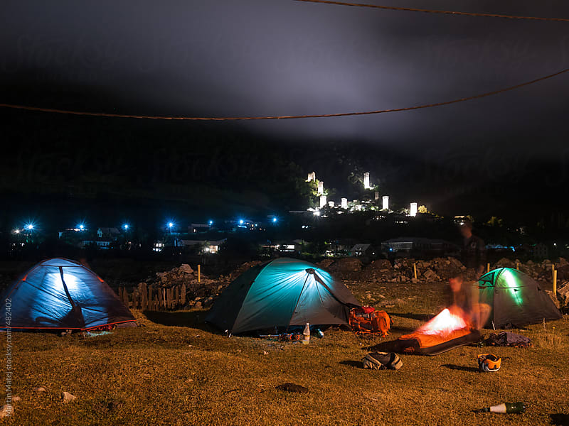 Glowing tents set up by the city at night by Martin Matej for Stocksy United