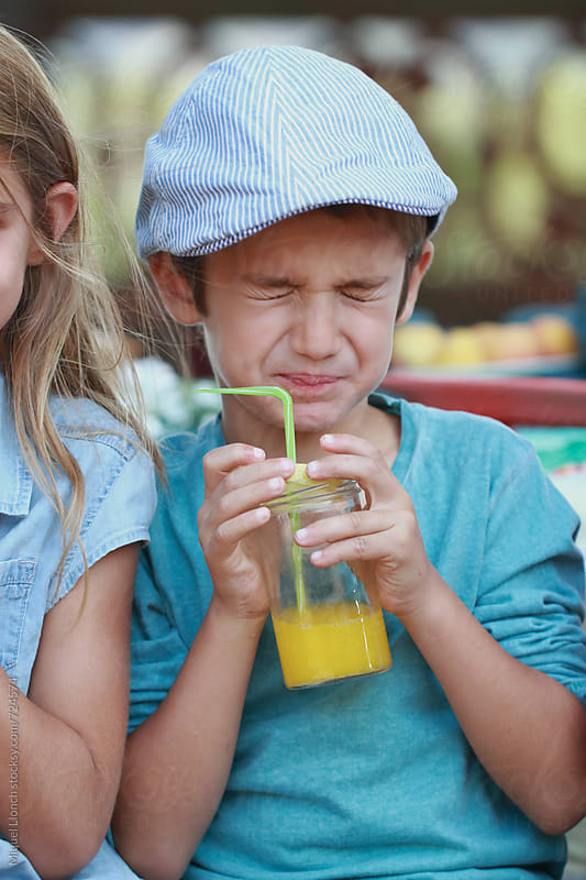 Funny expression face of a boy drinking fruit juice in a children's party by Miquel Llonch for Stocksy United