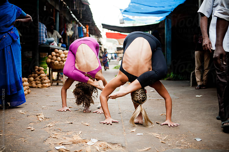 Two women doing yoga in a larket by Christine Hewitt for Stocksy United