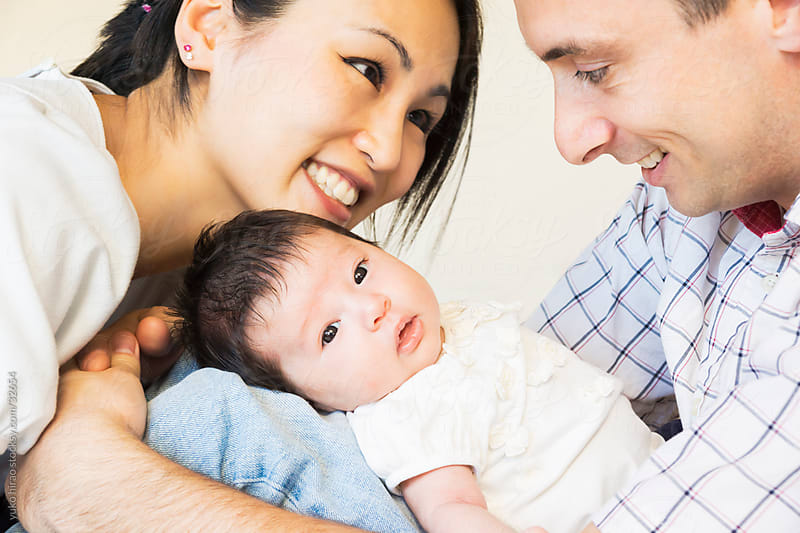 New interracial family portrait with newborn baby girl by yuko hirao for Stocksy United