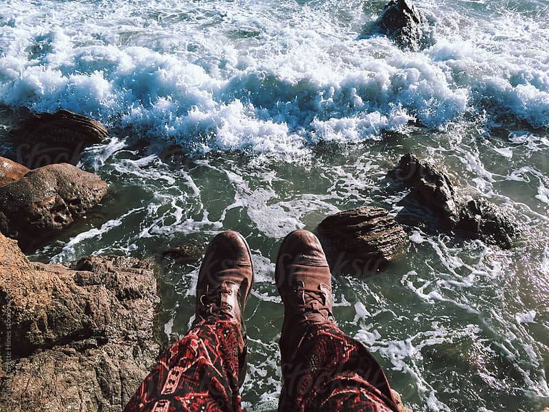 Feet hanging off a cliff towards the ocean  by Kristen Curette Hines for Stocksy United