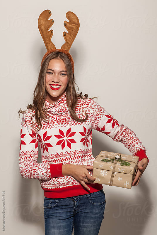 Woman With Reindeer Horns Holding Christmas Present by Mosuno for Stocksy United