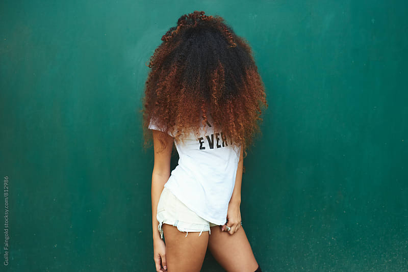 Photo of young afro woman standing against of green background by Guille Faingold for Stocksy United
