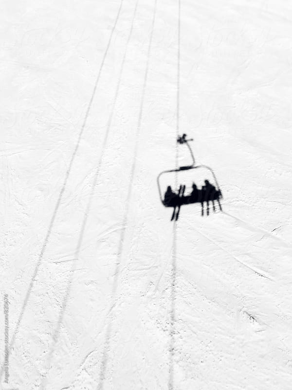 Shadow of three pople riding a chairlift on a groomed ski slope by Angela Lumsden for Stocksy United