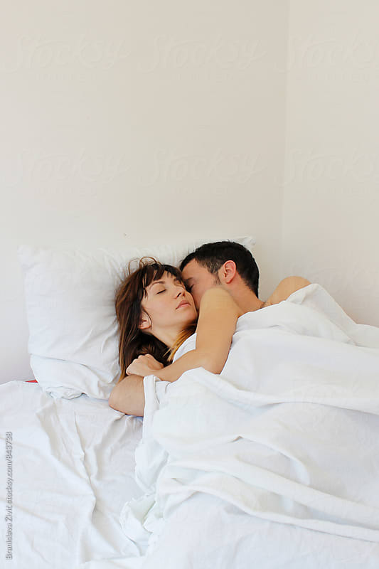 Portrait of a young couple having beautfiul morning in their bed by Evil Pixels Photography for Stocksy United