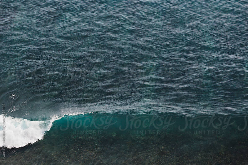 Ocean Wave breaking as it reaches the shallows  by Jovana Milanko for Stocksy United