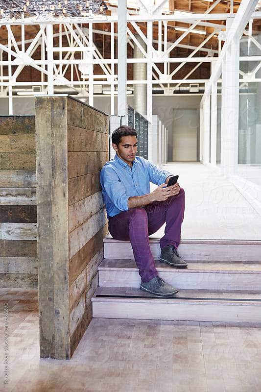 Portrait of millennial Indian businessman at tech start up office by Trinette Reed for Stocksy United