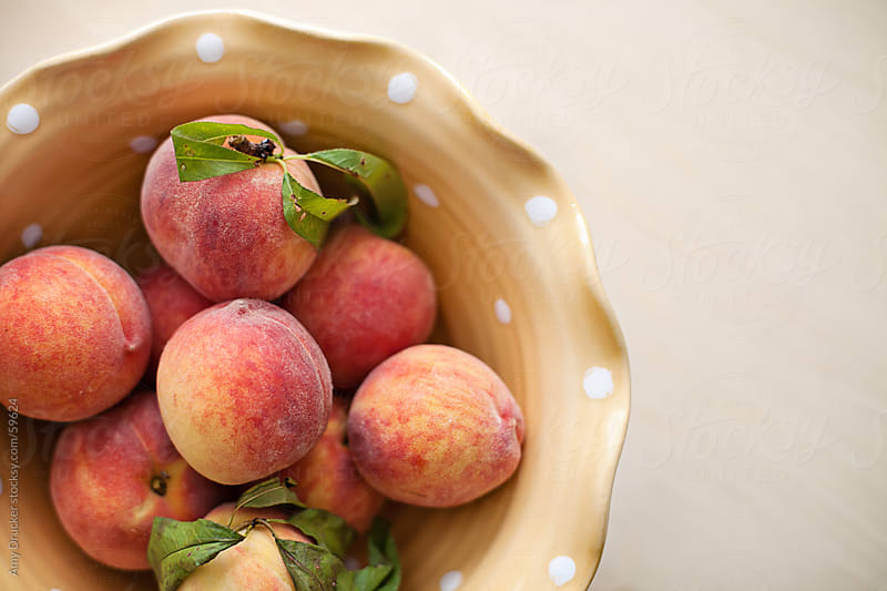 Fresh Peaches in a Polka-Dot Bowl by Amy Drucker for Stocksy United