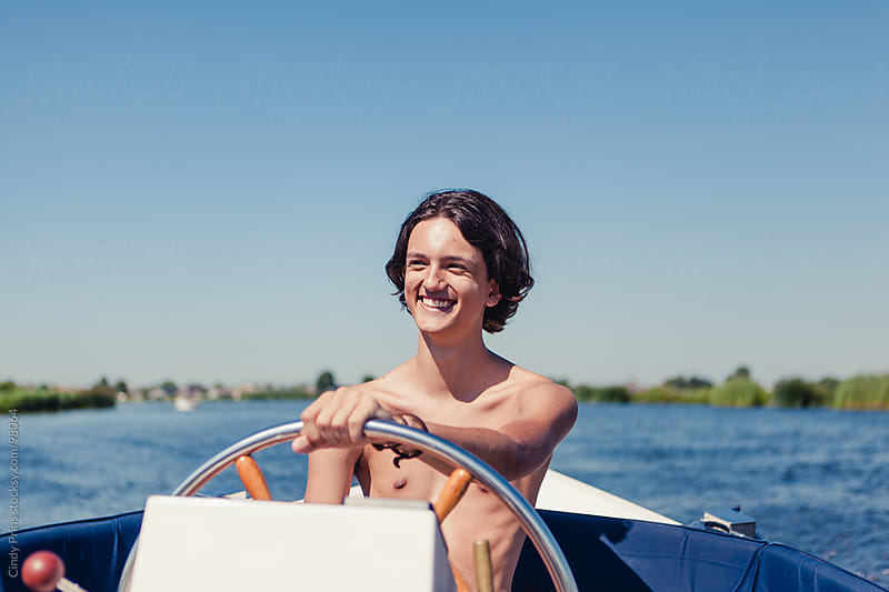 Teenage boy smiling behind the steering wheel of a boat on the lake by Cindy Prins for Stocksy United