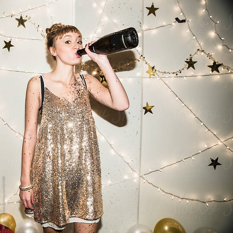 Pretty Girl drinking champagne out of the bottle by Shaun Robinson for Stocksy United