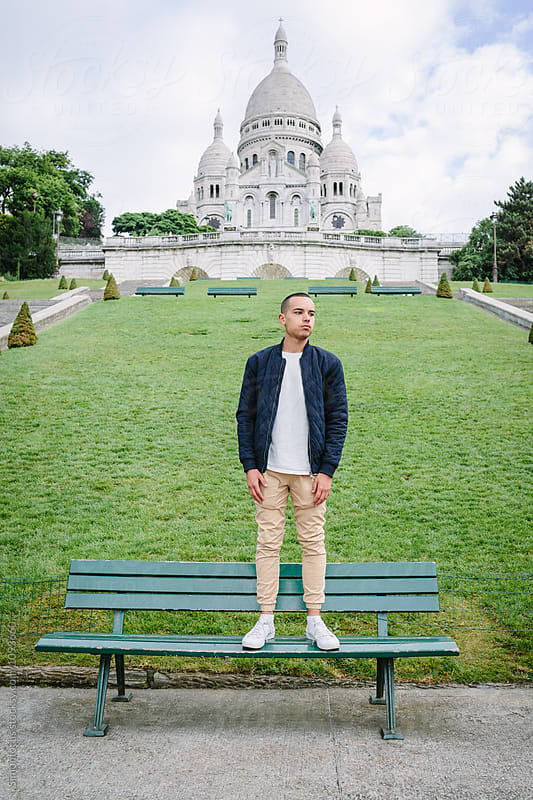 Young man on a bench, in Paris by Simonfocus for Stocksy United