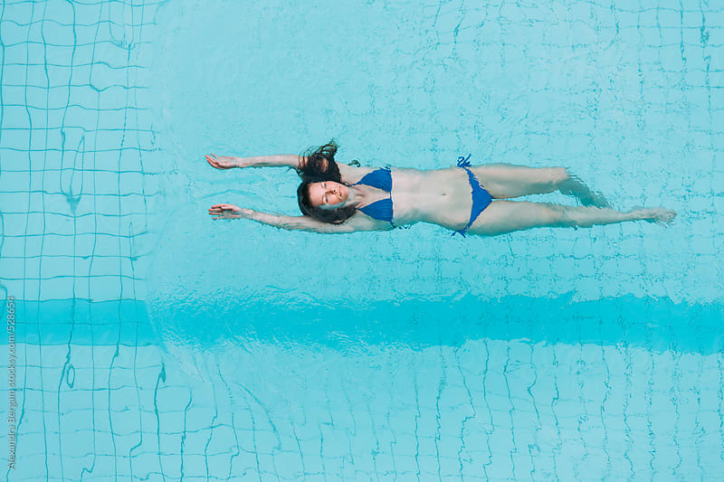 Woman in swimming pool   by Aleksandra Kovac for Stocksy United
