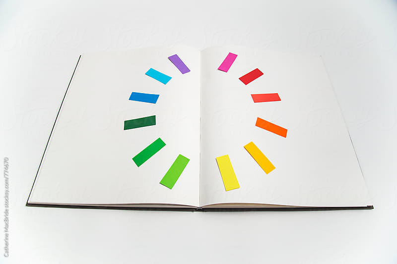 Colour wheel on an open book... by Catherine MacBride for Stocksy United