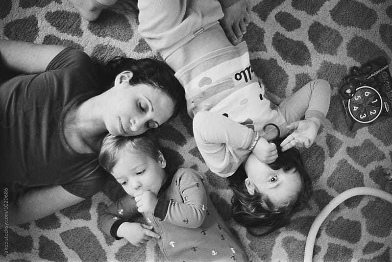 Mother laying on the floor with her children by Jakob for Stocksy United
