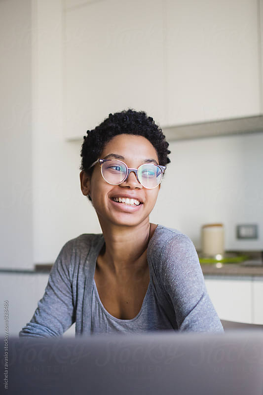 Portrait of smiling woman in front of her laptop by michela ravasio for Stocksy United