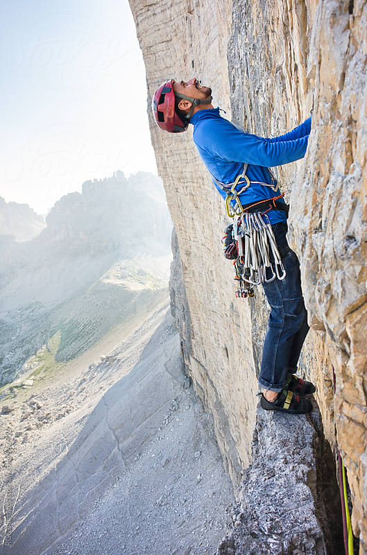 Alpinist standing on a narrow rock ledge rock climbing outdoor by RG&B Images for Stocksy United