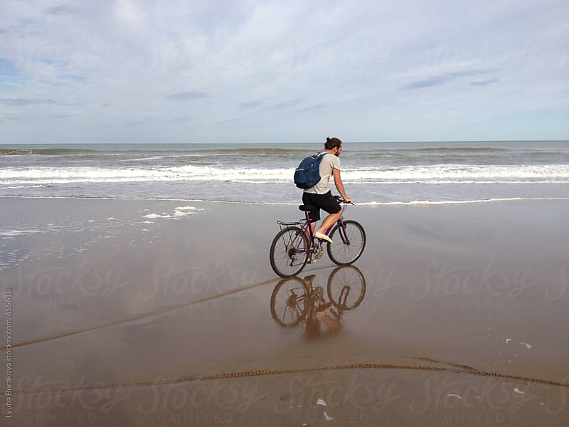 Man riding the bicycle on the beach of Atlantic ocean by Lyuba Burakova for Stocksy United