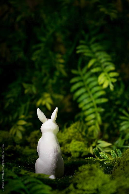 A white plastic bunny rabbit in the forest by J Danielle Wehunt for Stocksy United