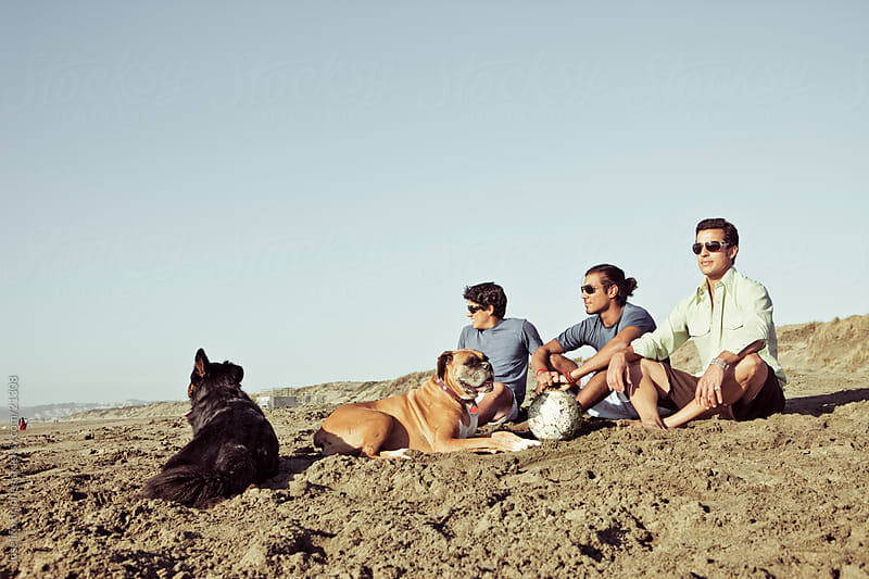 Hispanic/Latino Male Friends with their Dogs at the Beach by Joselito Briones for Stocksy United
