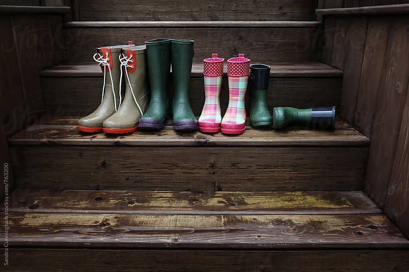 Rubber boots lined up outside on the back stairs by Sandra Cunningham for Stocksy United
