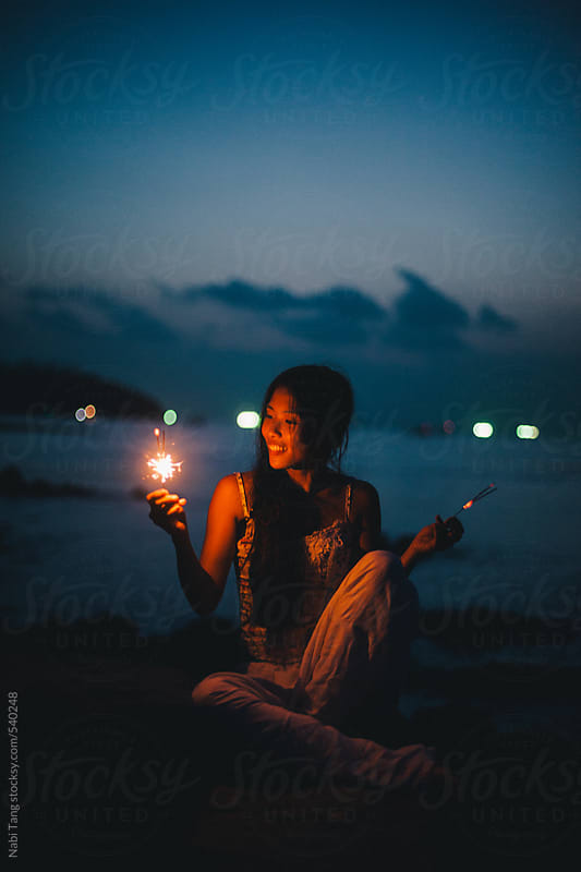 Beautiful young woman by the sea with sparkler in summer night by Nabi Tang for Stocksy United