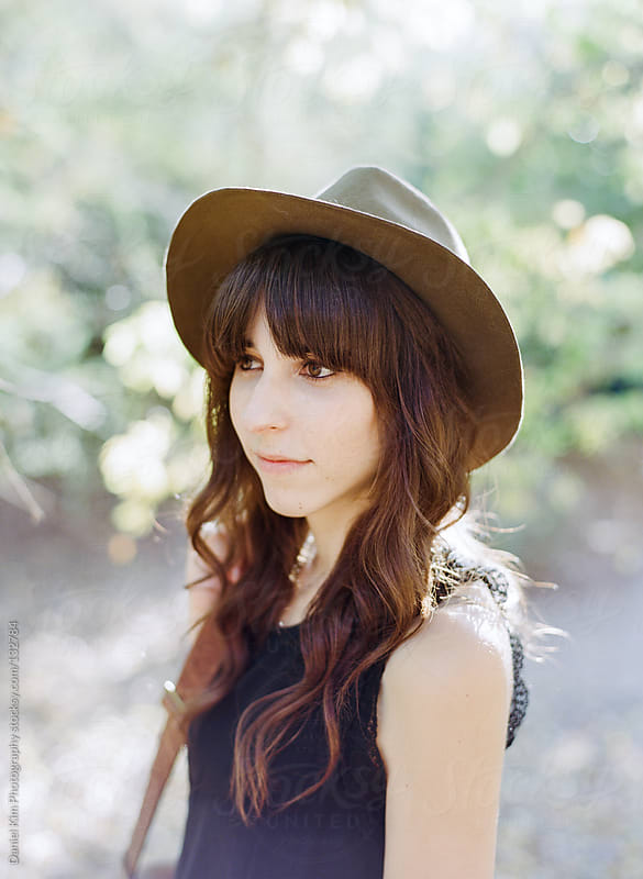 Portrait of young woman in hat by Daniel Kim Photography for Stocksy United