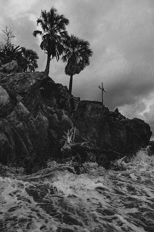 waves breaking on a cliff with cross on top, mexico by Jan Bijl for Stocksy United