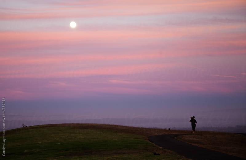 Female jogger exercising at dusk  by Carolyn Lagattuta for Stocksy United