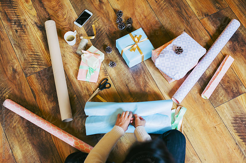 Overhead of a woman wrapping Christmas gifts at home. by BONNINSTUDIO for Stocksy United