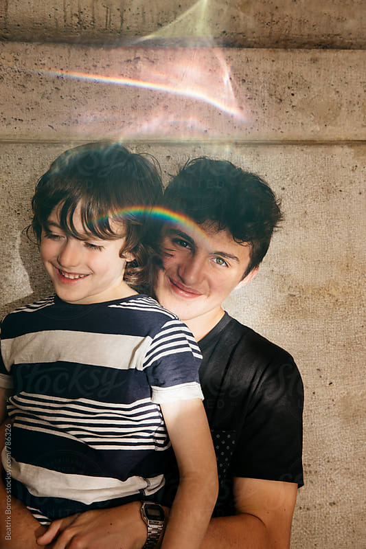 Portrait of a teenager boy and his brother with rainbow reflection by Beatrix Boros for Stocksy United