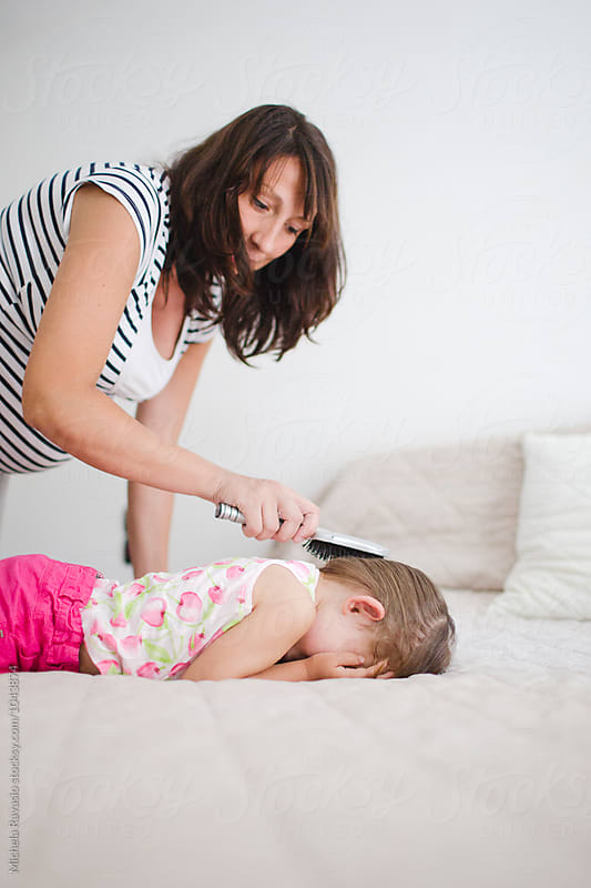 Pregnant mom combing her daughter by michela ravasio for Stocksy United