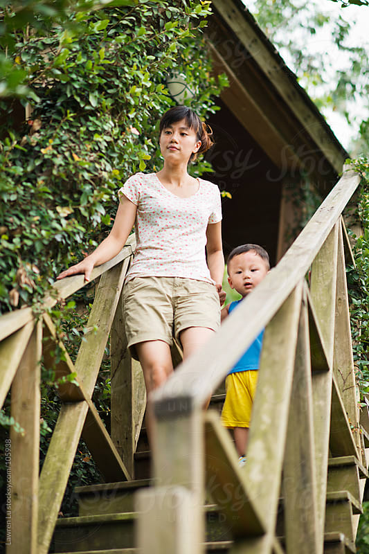 Mother and kid walk out from tree house by Lawren Lu for Stocksy United