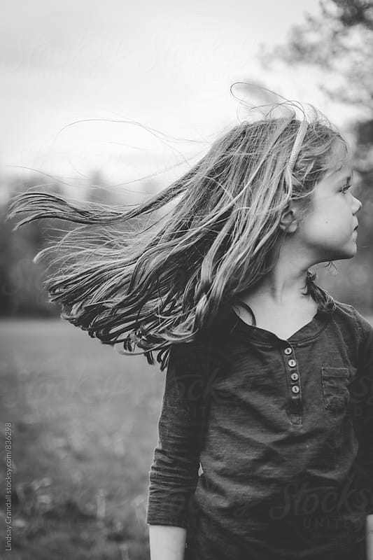 Child with hair blowing at park by Lindsay Crandall for Stocksy United
