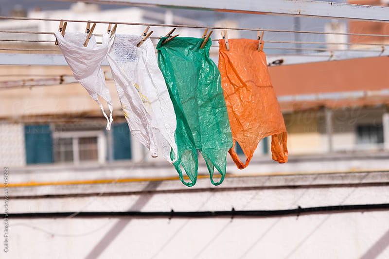 Plastic bags of different colors hanging on clothesline by Guille Faingold for Stocksy United