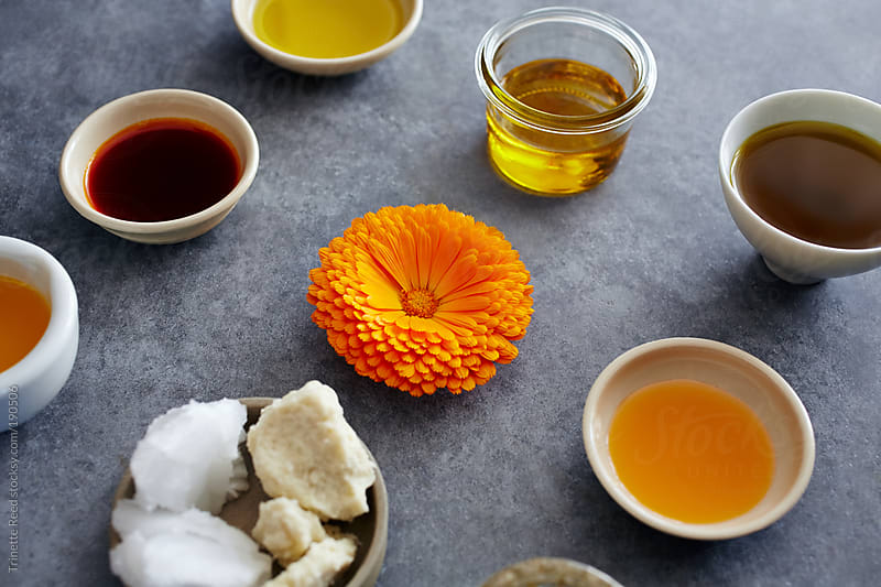 Calendula flower and various skincare oils on concrete by Trinette Reed for Stocksy United