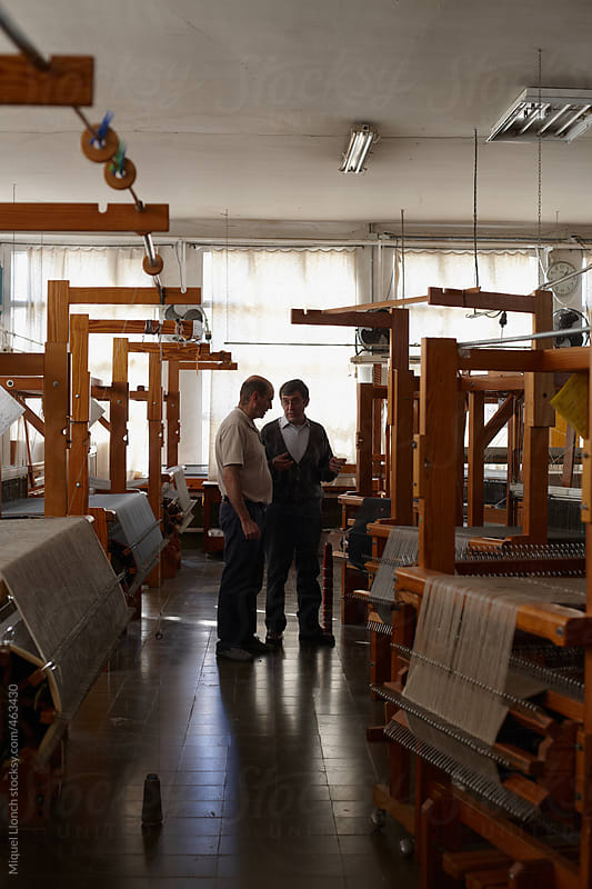 Two craftmen talking in a workshop of artisanal looms by Miquel Llonch for Stocksy United