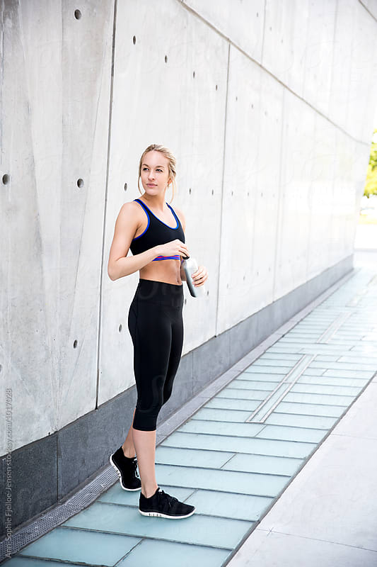 Woman relaxing on the sidewalk after workout by Ann-Sophie Fjelloe-Jensen for Stocksy United