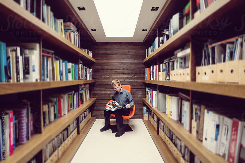 Solitary male in office library reading by Paul Phillips for Stocksy United