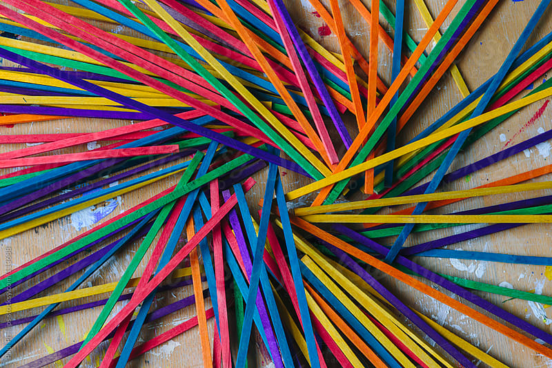 Craft sticks used in a school for art projects arranged in a circle. Vibrant colors by Paul Phillips for Stocksy United