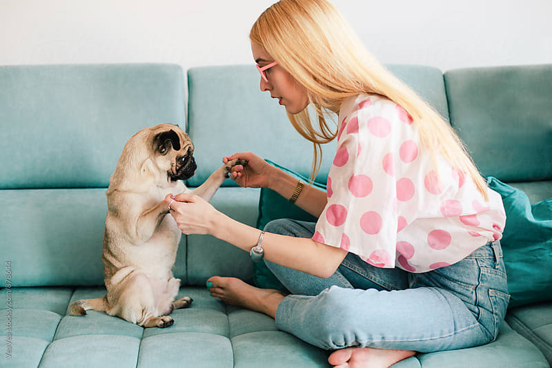 Blond woman having fun with her dog indoor by VeaVea for Stocksy United