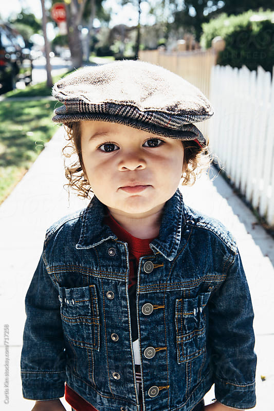 Cool toddler standing on sidewalk wearing newsboy cap by Curtis Kim for Stocksy United