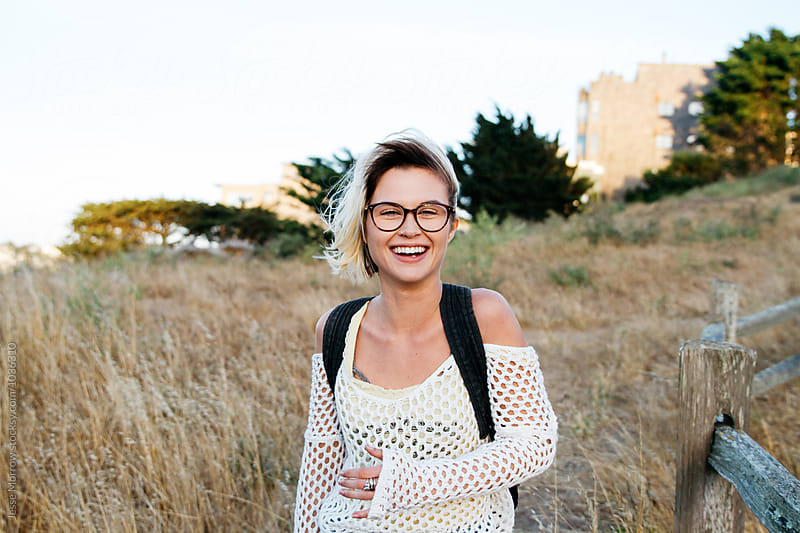 portrait of young female woman laughing in park with tall grass and fence by Jesse Morrow for Stocksy United