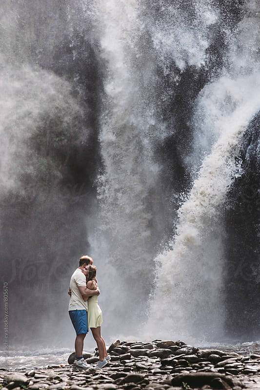 young couple standing in front of waterfall by Alexander Grabchilev for Stocksy United