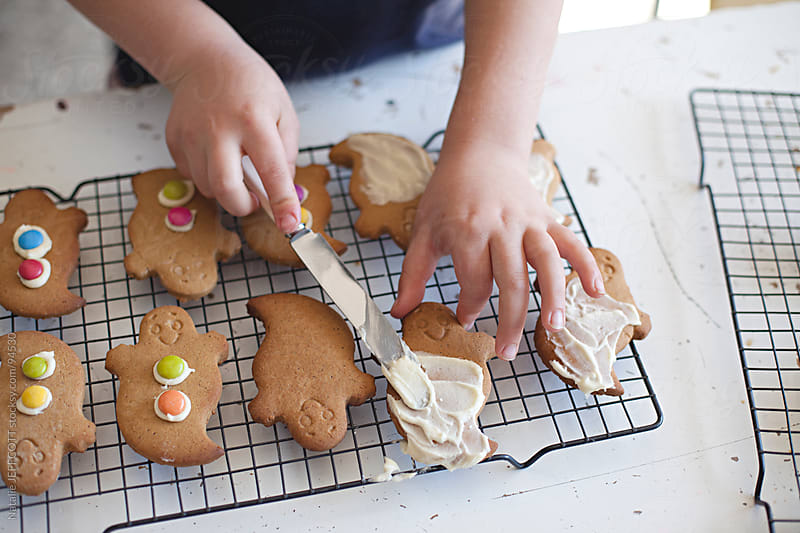 child icing ghost gingerbread cookies for Halloween by Natalie JEFFCOTT for Stocksy United