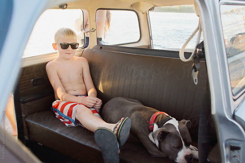 boy sits in backeseat of car with sleeping dog by Tana Teel for Stocksy United