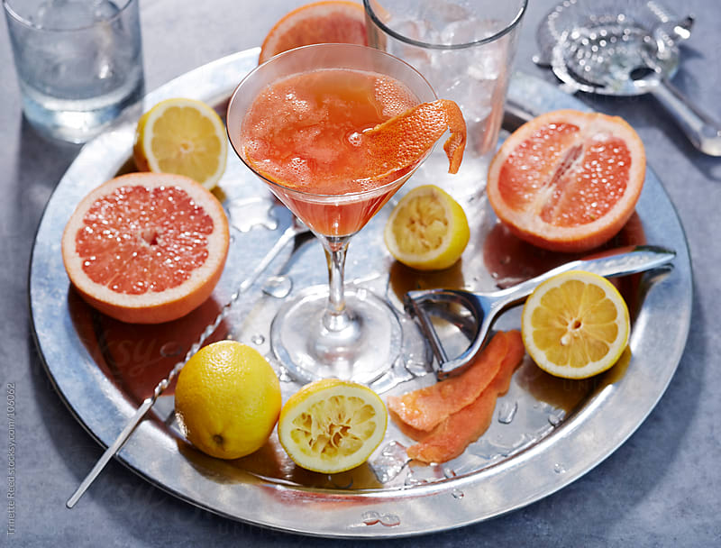 Mixed cocktail drink with grapefruit and lemon with ingredients by Trinette Reed for Stocksy United